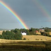 Regnbue over åkerlandskap