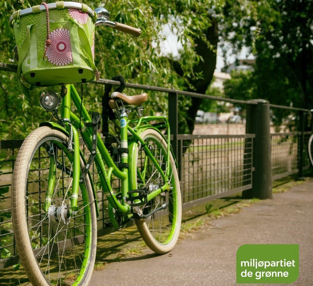 Grønn sykkel lent mot et gjerde